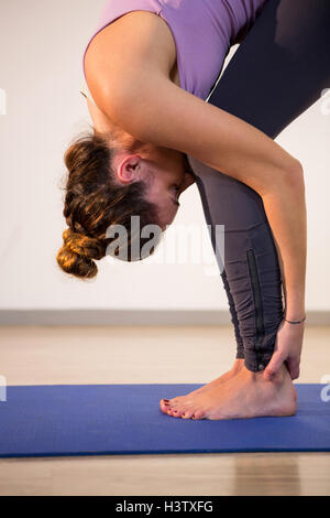 Woman performing standing forward bend - Stock Photo