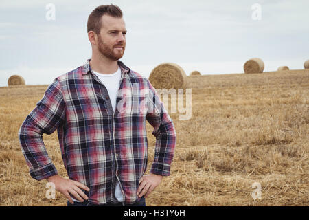 Farmer standing with hands on hips in the field - Stock Photo
