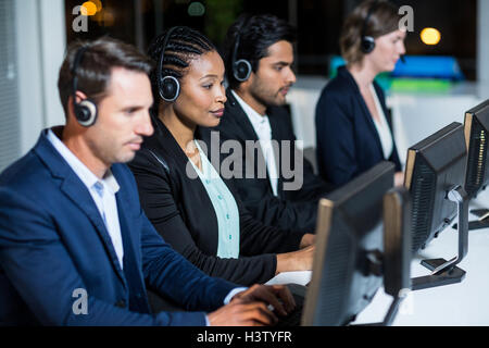 Colleagues with headsets using computer at office - Stock Photo