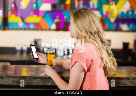 Beautiful woman using mobile phone while having beer - Stock Photo