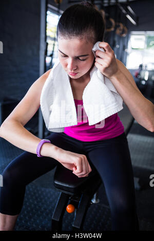 Young female athlete checking time in gym - Stock Photo