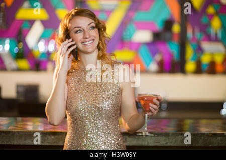 Young woman talking on mobile phone while having cocktail at counter - Stock Photo