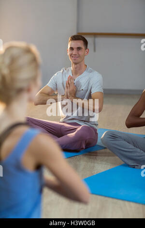 Instructor taking yoga class - Stock Photo