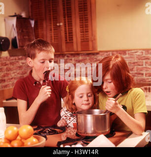 1970s 3 KIDS GIRLS BOY MAKING FUDGE BOY LICKING SPOON GIRL STIRRING PAN ON STOVE - Stock Photo