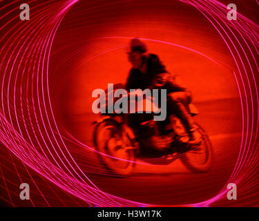 1970s ANONYMOUS MAN RIDING MOTORCYCLE RED GEL SPECIAL EFFECT MOTION SPEED SPORT MOTORCROSS - Stock Photo