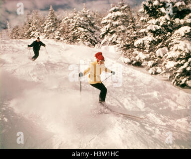 1960s 1970s TWO PEOPLE MAN WOMAN SKIING DOWN SNOWY SLOPE PINE TREES WOMAN WEARING YELLOW JACKET AND RED CAP - Stock Photo