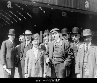 1900s GROUP OF MEN IN SUITS & HATS STANDING LOOKING AT CAMERA AT PENNSYLVANIA RAILROAD STATION IN PITTSBURGH PA - Stock Photo