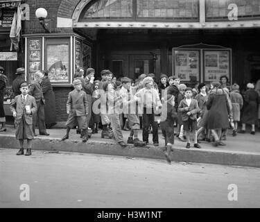 1920s 1930s NEIGHBORHOOD BOYS AND GIRLS WAITING TO GET INTO A MOVIE MATINEE IN WATERBURY CONNECTICUT USA - Stock Photo