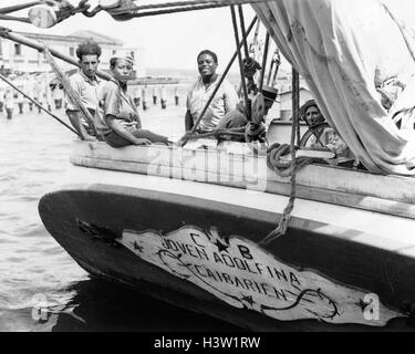 1930s 1940s MEN AND BOY AT STERN OF TRADING SCHOONER LOOKING AT CAMERA HAVANA CUBA - Stock Photo