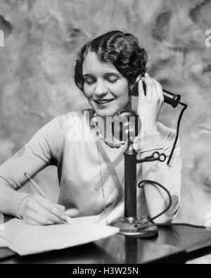 1920s SMILING WOMAN SITTING AT DESK WRITING AND TALKING ON CANDLESTICK TELEPHONE - Stock Photo