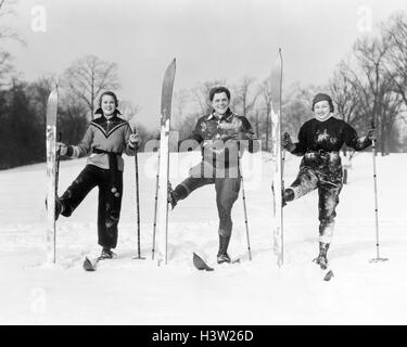 1930s TWO WOMEN AND A MAN LOOKING AT CAMERA SMILING POSING ON SKIS WITH RIGHT SKI TURNED UPRIGHT - Stock Photo