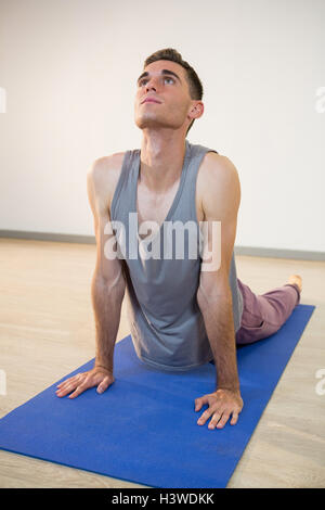 man doing cobra pose with his yoga partner stock photo