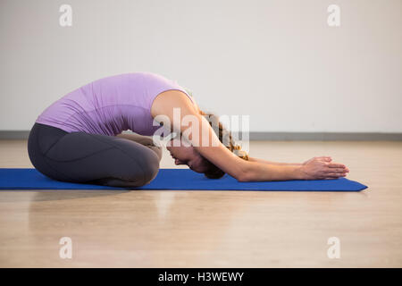 Woman doing yoga child pose on exercise mat - Stock Photo
