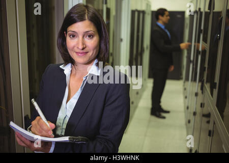 Technician maintaining record of rack mounted server in paper - Stock Photo