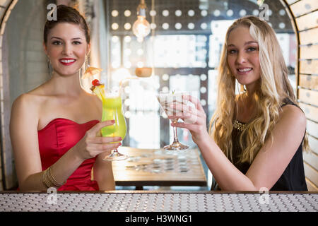 Female friends holding glass of cocktail in bar - Stock Photo