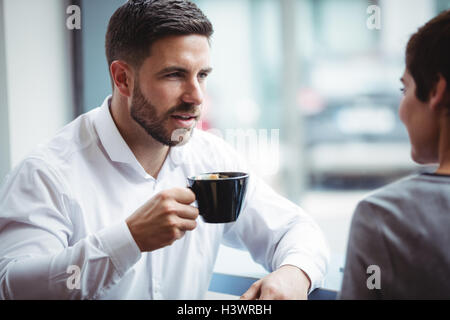 Businesspeople interacting while having coffee - Stock Photo