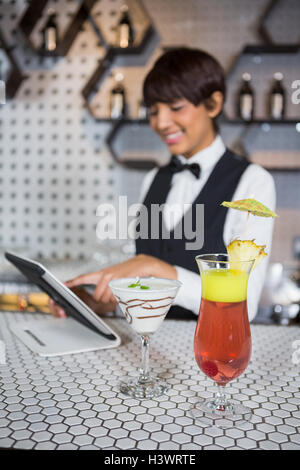 Waitress using digital tablet with glass of cocktail in bar counter - Stock Photo