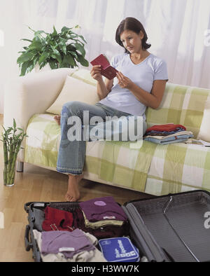 Sitting rooms, woman, holiday preparations, passport, look at, model released, vacations, travel, holiday trip, - Stock Photo