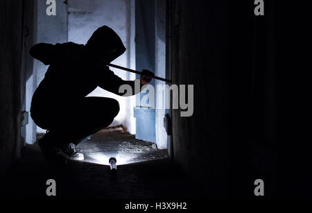 Rottweil, Germany. 8th Oct, 2016. ILLUSTRATION - A ficticious burglar breaks open a door with a jemmy in the basement - Stock Photo