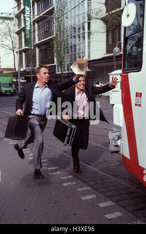 Town, manager, two, run, miss streetcar, run, outside, miss, missed, too late, briefcases, detain, hurry, there - Stock Photo