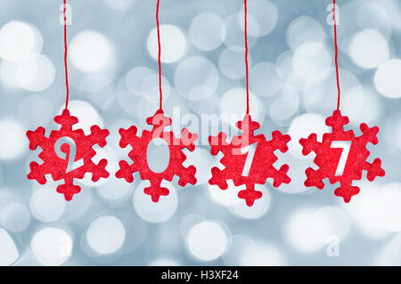 2017 cut in red fabric christmas ornaments hanging on bokeh background, 2017 new year decoration - Stock Photo