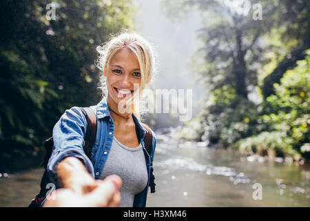 Smiling young woman holding man's hand and leading him in the forest hike. Point of view shot of couple by the creek. - Stock Photo