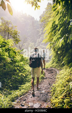 Rear view shot of young couple walking along a path through the tree. Man and woman hiking on forest trail. - Stock Photo