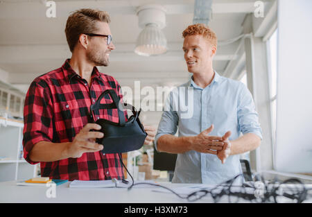 Shot of two young developers discussing on new virtual reality glasses. Business colleagues working on developing new VR goggles