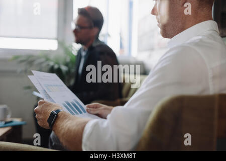 Shot of business people sitting in office and going through business reports. Businessman reading charts during - Stock Photo