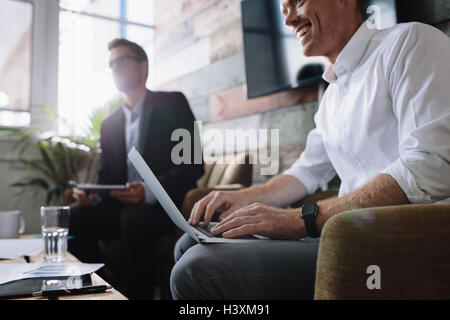 Happy young executive working on laptop at corporate meeting. Businessman using laptop in meeting with corporate - Stock Photo