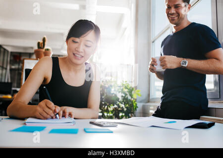 Young asian woman writing notes with male colleague standing by with cup of coffee. Business colleagues working - Stock Photo