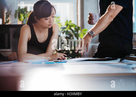 Two young executives discussing new business ideas in office. Colleagues working together on paperwork. Woman sitting - Stock Photo