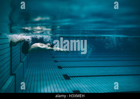 Underwater shot of male swimmer turning over in swimming pool. Pro male swimmer in action inside pool. - Stock Photo
