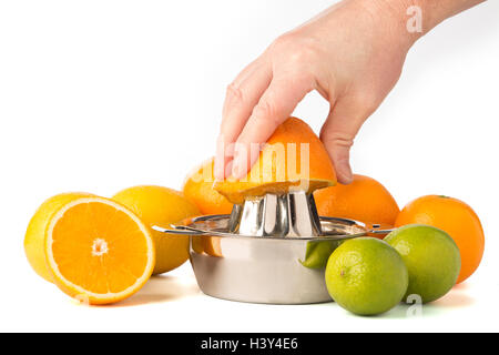 Hand extracting an orange in stainless steel citrus juicer surrounded by whole citrus fruits. - Stock Photo