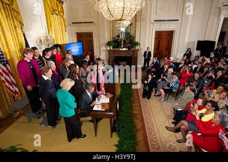 U.S President Barack Obama signs executive actions to strengthen enforcement of equal pay laws for women, at an - Stock Photo