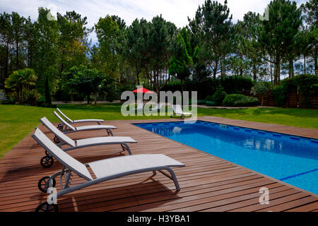 Deckchairs next to outdoor swimming pool - Stock Photo