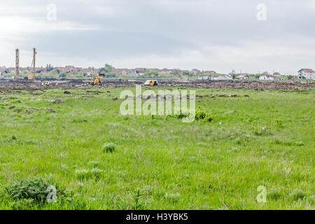 Landscape transform into urban area with machinery, people are working. View on  construction site - Stock Photo
