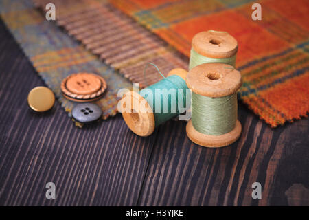 Thimble, buttons, spools of thread and fabric swatches on a wooden background close up - Stock Photo