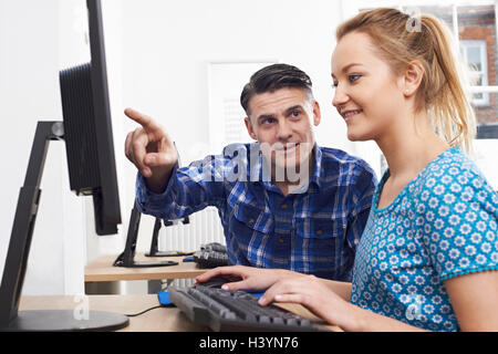 Man Training Woman On Computer In Office - Stock Photo
