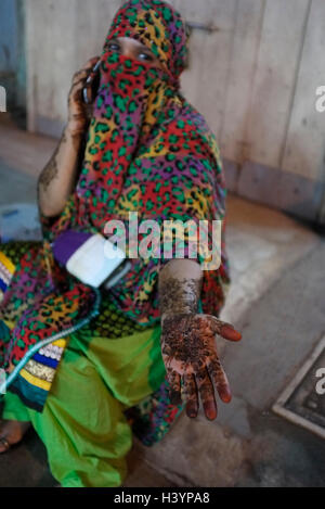 a Women in Saree and burka (burqa) speaks by mobile telephone with Mehndi  (henna) tattoos on arm and hands. Kurla, - Stock Photo