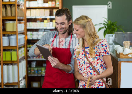 Male staff and woman looking at digital tablet - Stock Photo