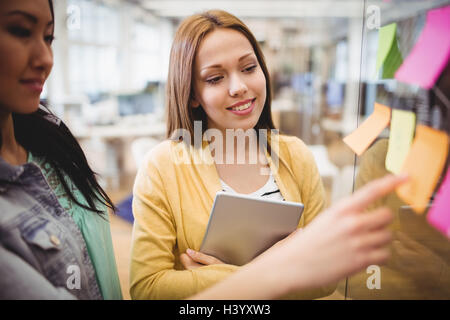 Photo editor with female coworker looking at sticky notes - Stock Photo