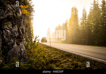 morning fog and tractor in norwegian forest during autumn - Stock Photo