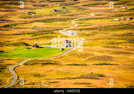 long and winding road with red houses during autumn in norway - Stock Photo
