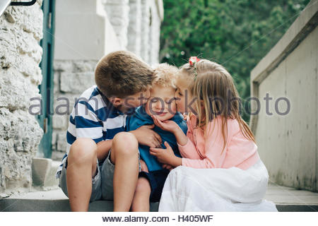 Boy and girl sitting on a step kissing their brother on the cheek - Stock Photo
