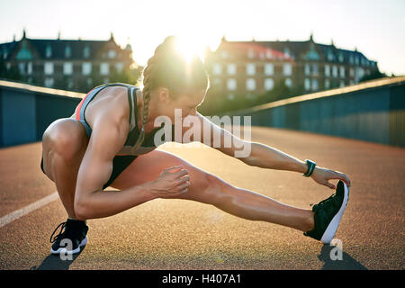 Female jogger stretches one muscular leg while placing all her weight on the other - Stock Photo