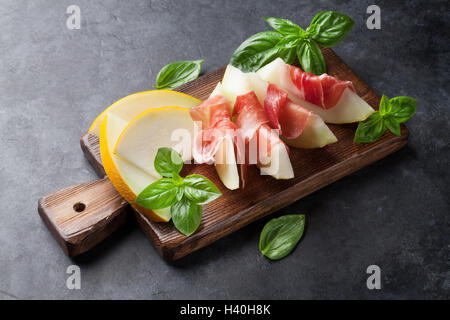 Fresh melon with prosciutto and basil. Antipasti. - Stock Photo