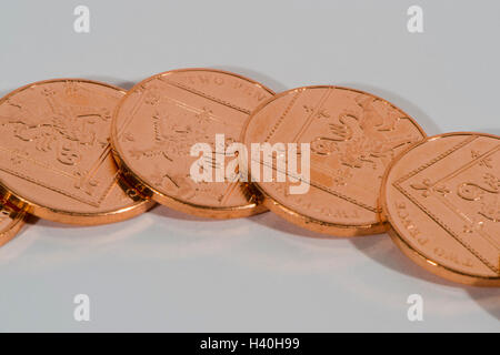 Laid flat and overlapping, 4 shiny, copper, two pence, UK coins, tails up - loose-change and money with little value. - Stock Photo