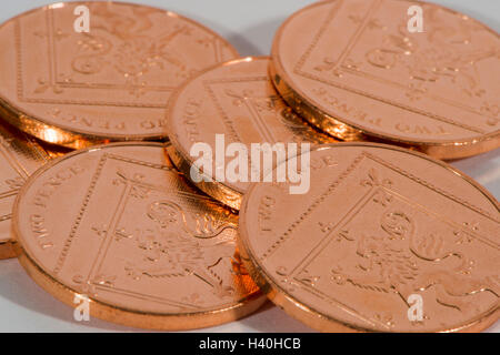 Laid flat and overlapping, 6 shiny, copper, two pence coins, tails up - loose-change and UK money with little value. - Stock Photo