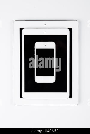 Different graphic tablets and mobile phone on white background - Stock Photo